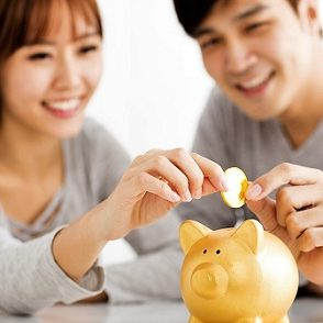 Young couple placing coin into gold piggy bank