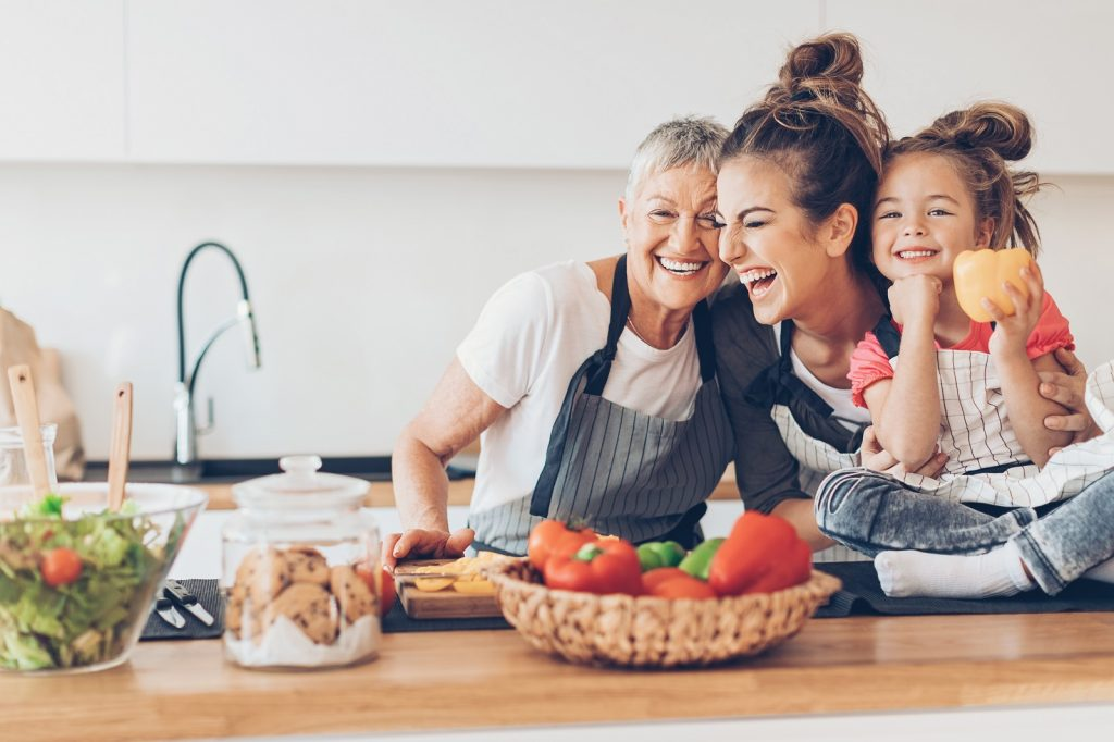 Three generations women laughing in the kitchen photo