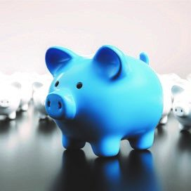 Big blue piggy bank with small white piggy bank in background.