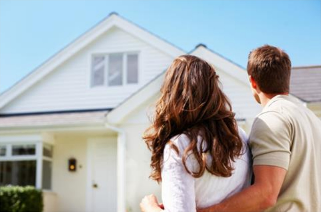 Man with arm around woman while looking at a new house