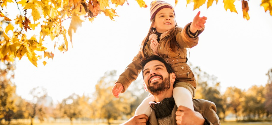 Dad and child enjoying walk in the fall