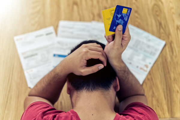 an ariel view of a stressed out man holding credit cards next to a table of bills