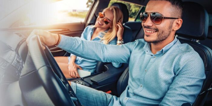 man and woman in summer driving a car